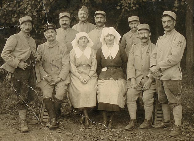 "Alice O'Brien (right) and her friend, Doris Kellogg, posed with a group of men during World War I. ""My hands are behind me,"" O'Brien said, ""because they were covered with doughnut dough."" Photo courtesy of Alvina O'Brien / Minnesota Historical Society"