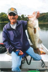 Dave Nimmer, who cherishes the serenity of his fishing trips this time of year, shows off a freshwater catch — a bass he caught and released.