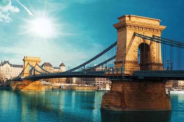 The Szechenyi Chain Bridge spans the Danube River in Budapest, Hungary, one of many cities offering homestay options such as Airbnb.